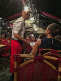 Waiter talks with diner at a Paris cafe at night Stock Images