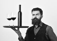 Waiter with tray, bottle and glass of red wine. Barman with confident face holds italian drink. Man with beard and mustache holds alcohol on white background Royalty Free Stock Photography