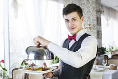 Waiter. With a tray of food in the restaurant hall royalty free stock photography