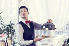 Waiter. With a tray of food in the restaurant hall Stock Photos