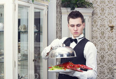 Waiter. With a tray of food in the restaurant hall Stock Image