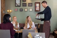 Waiter With Tray Of Glasses While Female Customers. Young waiter with tray of glasses while female customers having meal in restaurant Stock Image