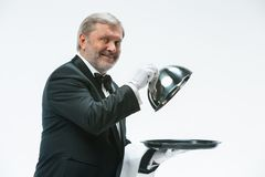 The waiter with tray and metal cloche lid cover. The senior waiter holding white towel and standing isolated on white studio background with tray and metal Royalty Free Stock Photo