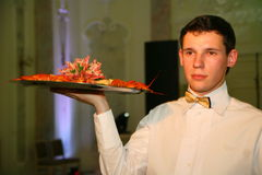 The waiter with the tray in a Russian restaurant. The waiter brings exclusive artfully decorated dish of boiled red crayfish and seafood cocktail from the chef stock photos
