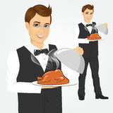 Waiter with tray serving roasted poultry. Portrait of young handsome waiter with tray serving roasted poultry Stock Photography