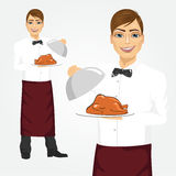 Waiter with tray serving roasted poultry. Portrait of young handsome waiter with tray serving roasted poultry Royalty Free Stock Images