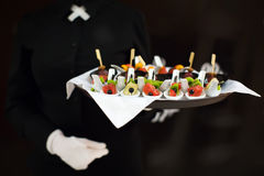 A waiter with a tray of snacks at a banquet royalty free stock photo