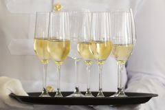 Waiter tray white wine. Waiter holds a tray of white wine, champagne and water royalty free stock photos