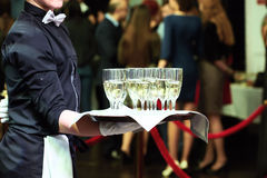 Waiter with tray and wine glasses at party. Catering or celebration concept. Waiter holding a tray with glasses of vine at party royalty free stock images