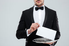 Waiter in tuxedo with bowtie holding blank card on tray Stock Photography