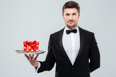 Waiter in tuxedo with bowtie holding present box on tray. Attractive young waiter in tuxedo with bowtie holding present box on tray Stock Photos