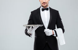 Waiter in tuxedo holding metal empty tray and napkin. Closeup of young waiter in tuxedo holding metal empty tray and napkin Stock Photos