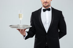 Waiter in tuxedo holding tray with glass of champagne Stock Photography