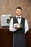 Waiter in uniform with food cloche. In a hotel restaurant Royalty Free Stock Photos