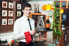 Waiter in uniform at restaurant. Handsome man waiter in uniform with tray and wine at restaurant royalty free stock image