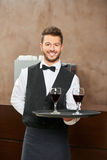 Waiter in uniform serving red wine royalty free stock photography