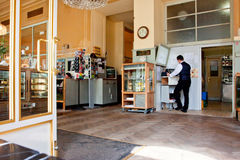 Waiter in uniform stands at the cash register in the old cafe Royalty Free Stock Photo