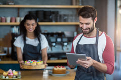 Waiter using digital tablet at counter in café Stock Images