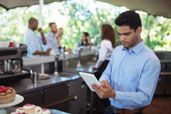 Waiter using digital tablet at outdoors cafe Royalty Free Stock Photos