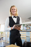 Waiter using digital tablet in restaurant Stock Photo