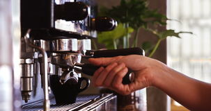 Waiter using a tamper to press ground coffee into a portafilter stock video