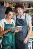 Waiter and waitress discussing over digital tablet Stock Photo