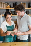 Waiter and waitress discussing over digital tablet Royalty Free Stock Images