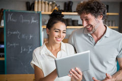 Waiter and waitress discussing over digital tablet Stock Photos