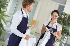 Waiter and waitress drying glasses in restaurant royalty free stock photography