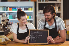 Waiter and waitress holding chalkboard at counter Royalty Free Stock Photography