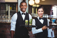 Waiter and waitress holding a serving tray with glass of cocktail Royalty Free Stock Photography
