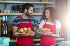 Waiter and waitress holding a tray of croissants and cake Stock Images