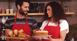 Waiter and waitress holding a tray of croissants and cake stock footage