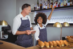 Waiter and waitress interacting with each other at counter Royalty Free Stock Photo