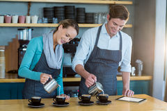 Waiter and waitress making cup of coffee at counter in cafe Stock Photo