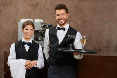 Waiter and waitress serving drinks stock photo