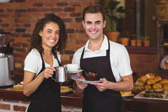 Waiter and waitress smiling at camera royalty free stock photo
