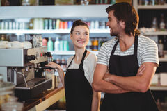 Waiter and waitress smiling at each other. In cafe Royalty Free Stock Photography