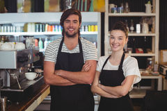 Waiter and waitress standing with arms crossed in cafe. Portrait of waiter and waitress standing with arms crossed in cafe Stock Images