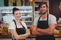 Waiter and waitress standing with arms crossed in cafe. Portrait of waiter and waitress standing with arms crossed in cafe Stock Photo