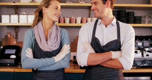 Waiter and waitress standing with arms crossed and smiling at each other stock video