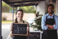 Waiter and waitress standing with chalkboard with open sign. Outside the cafe Stock Image