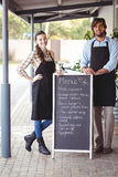 Waiter and waitress standing with menu board outside the cafe Royalty Free Stock Images