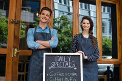 Waiter and waitress standing with menu board outside the cafe royalty free stock photography
