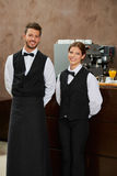 Waiter and waitress in uniform. Smiling waiter and waitress in uniform in a restaurant Stock Photo