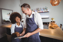 Waiter and waitress using digital tablet at counter Stock Photos