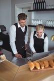 Waiter and waitress using laptop at counter Stock Photo