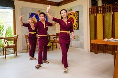 Waiter and waitress wearing uniform in the thai restaurant performing traditional dance. In Maldives stock photography