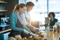 Waiter and waitress working at counter in café Stock Photo