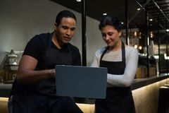 Waiter and waitresses discussing over laptop at counter Royalty Free Stock Photography